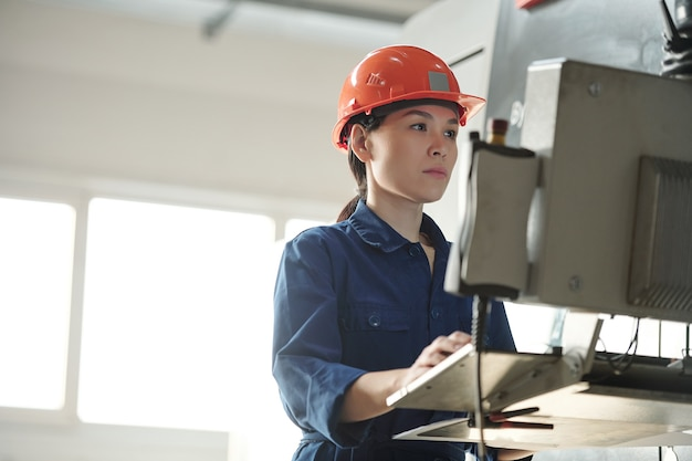 ワークショップでセットアップを選択しながら、産業機械のコンピューターを使用してヘルメットの深刻な若いアジアのオペレーター