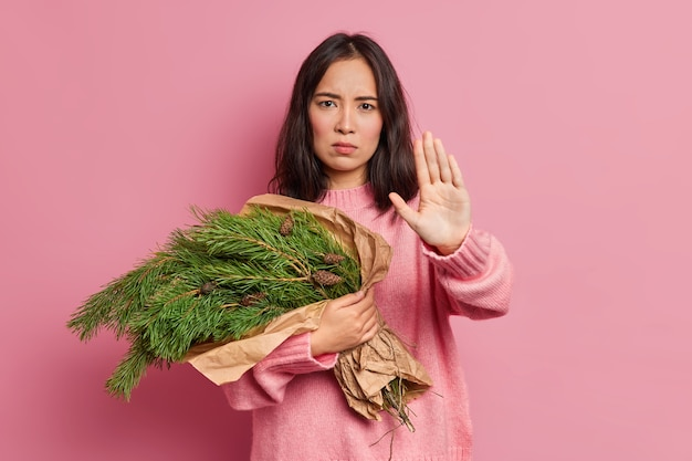Serious young asian woman keeps palm outstretched at camera demonstrates stop gesture prevents you holds spruce fir tree branches with pine cones going to decorate house on new year and christmas