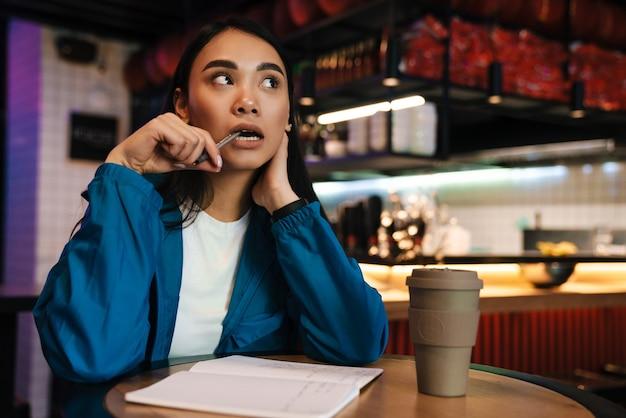 プランナーでメモを取り、カフェに座って考えている深刻な若いアジアの女性
