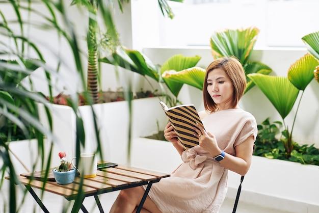Серьезная молодая азиатская женщина, читающая увлекательную книгу за столиком в кафе
