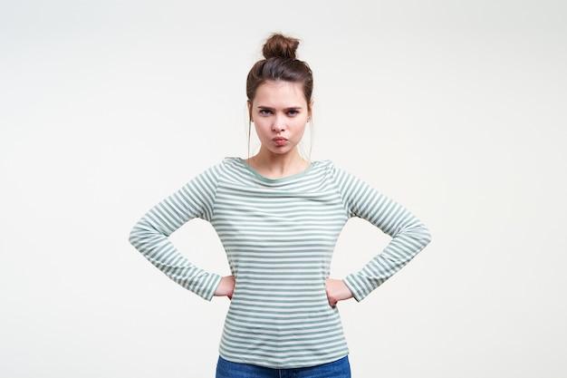 Giovane donna castana attraente seria con l'acconciatura casuale che guarda trasversalmente davanti e che tiene le mani sulla sua vita mentre posa sopra la parete bianca