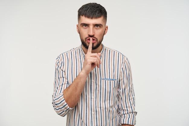Серьезный молодой привлекательный темноволосый бородатый мужчина с модной стрижкой, поднимающий указательный палец в жесте молчания, позируя над белой стеной в полосатой рубашке