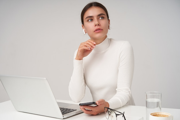 Serious young attractive dark haired lady dressed in white poloneck keeping smartphone in her hand while waiting for colleagues at conference room, isolated over white wall