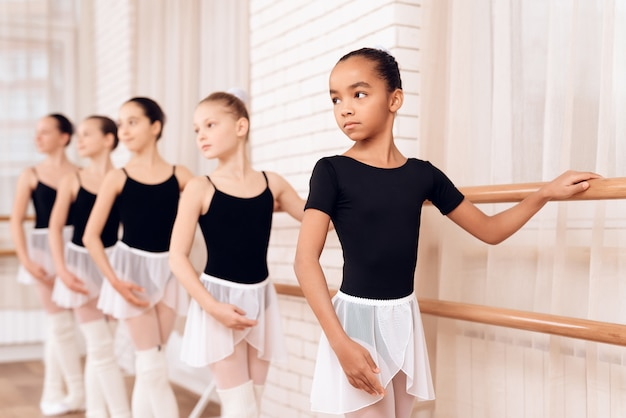 Serious young ballerinas stand along ballet barre.