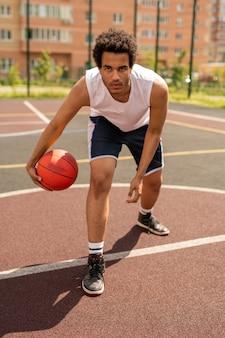 코트에 흰색 선으로 서있는 동안 공을 던질 심각한 젊은 농구 선수