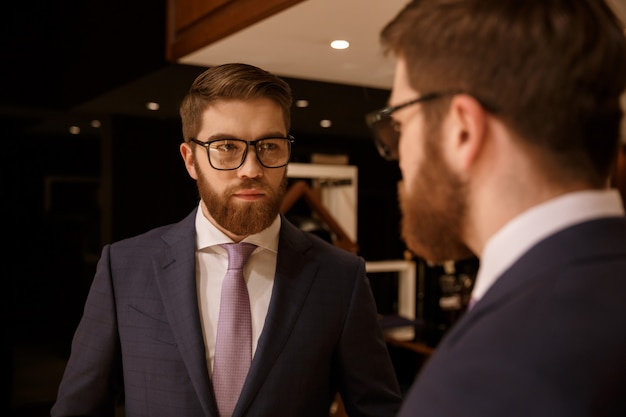 Serious young bearded businessman looking at mirror