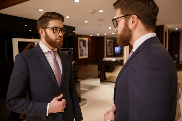 Serious young bearded businessman standing indoors