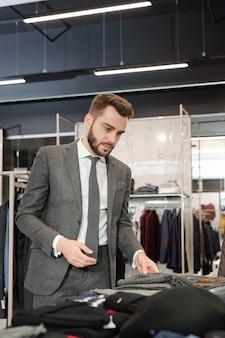 Серьезный молодой бородатый бизнесмен с салфеткой в кармане куртки трогает ткань одежды, выбирая одежду в магазине