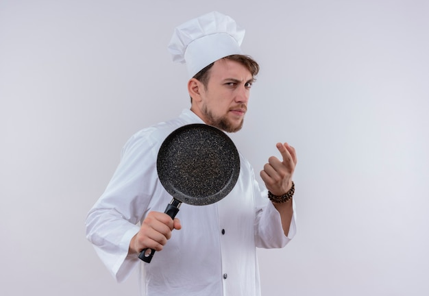 A serious young bearded chef man wearing white cooker uniform and hat holding frying pan like a baseball bat on a white wall