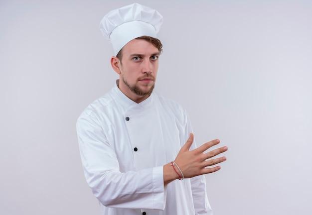 Un uomo barbuto giovane serio del cuoco unico che porta l'uniforme bianca del fornello e il cappello che alza la mano mentre osserva su una parete bianca