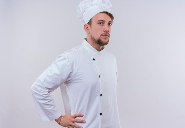 Un serio giovane barbuto uomo chef in uniforme bianca tenendo la mano sulla sua vita mentre guarda su un muro bianco