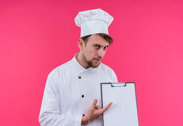 Un serio giovane barbuto chef uomo in uniforme bianca che punta alla cartella vuota mentre guarda su una parete rosa