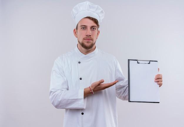 Un serio giovane barbuto uomo chef in uniforme bianca che mostra cartella vuota mentre guarda su un muro bianco