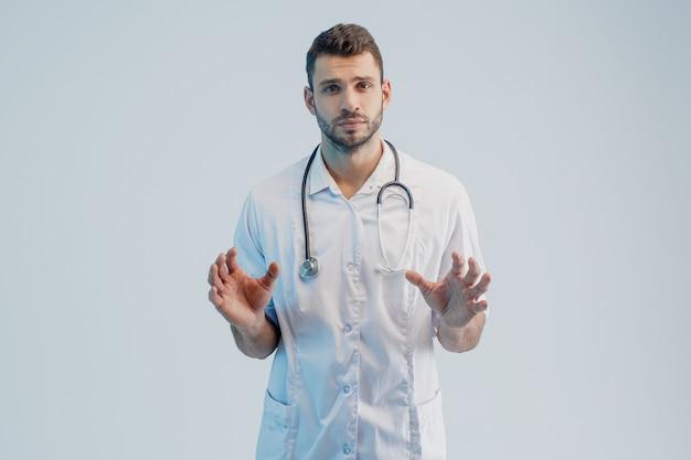 Портрет серьезный молодой бородатый европейский мужской доктор. человек в белом халате со стетоскопом. изолированные на сером фоне с бирюзовым светом. студийная съемка. скопируйте пространство.