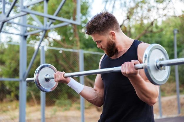 Серьезный молодой бородатый фитнес-мужчина, поднимающий штангу на открытом воздухе