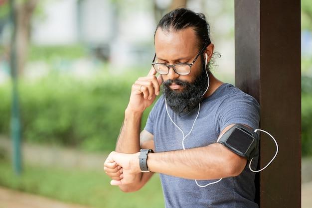 야외에 서서 스마트워치로 오디오 메시지를 들으면서 이어폰을 조정하는 안경을 쓴 수염난 인도 남자