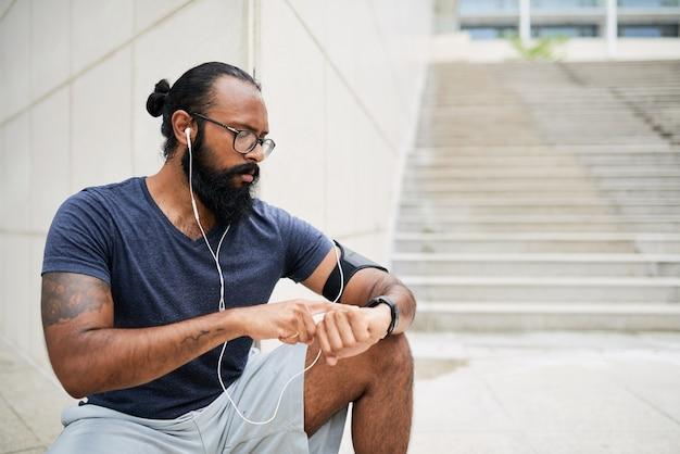 문신을 한 수염난 인도 남성이 건물 모퉁이에 앉아 훈련 후 피트니스 시계를 확인합니다.