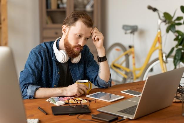 Серьезный молодой бородатый мужчина сосредоточился на концепции дизайна, сидя за столом и глядя на эскиз на экране ноутбука
