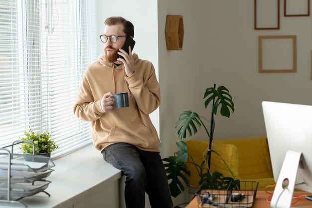 Серьезный молодой бородатый мужчина в очках сидит на подоконнике и смотрит через жалюзи, общаясь по телефону