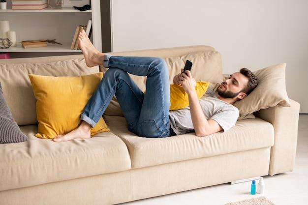 Серьезный молодой бородатый мужчина в джинсах лежит на диване и общается онлайн через мессенджеры на смартфоне в домашней изоляции