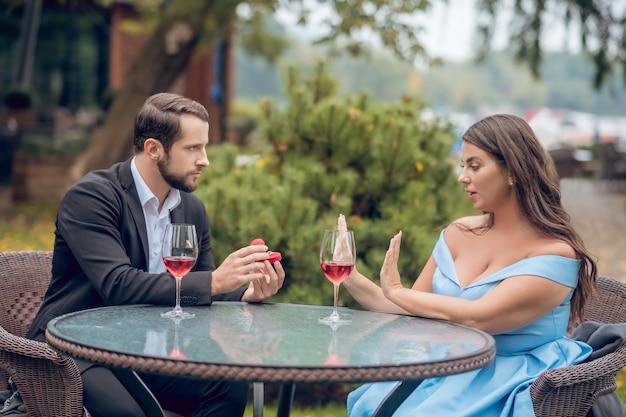 Серьезный молодой бородатый мужчина в костюме дает кольцо и красивая женщина в праздничном платье отказывается сидеть в летнем кафе