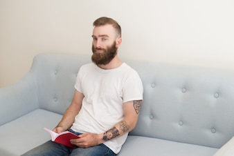 Serious young bearded man sitting on sofa and reading book