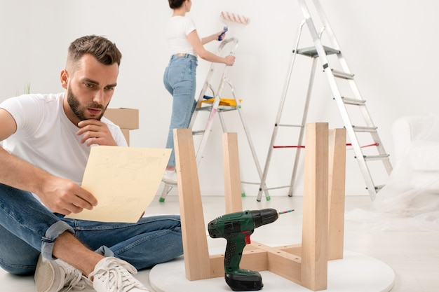 Serious young bearded man sitting with crossed legs on floor and reading instruction while assembling furniture in new apartment
