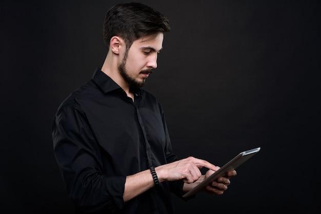 Серьезный молодой бородатый мужчина стоит у черной стены и анализирует данные на планшете