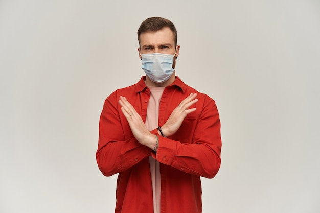 Serious young bearded man in virus protective mask on face against coronavirus makes x shape with hands and arms and showing stop sign over white wall