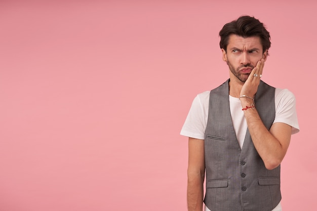 회색 양복 조끼와 흰색 티셔츠를 입고 검은 머리를 가진 심각한 젊은 수염 난 남자, 분홍색 배경 위에 서서, 뺨에 손바닥으로 찡그린 채로 옆으로보고