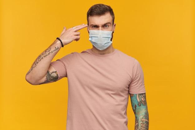 감염을 방지하기 위해 분홍색 티셔츠와 위생 마스크에 문신이있는 심각한 젊은 수염 난 남자는 노란색 벽 위에 사원 근처의 총처럼 손가락을 유지합니다.