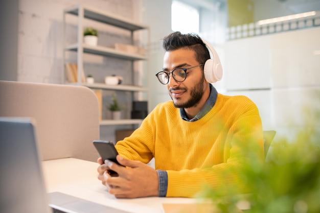 机に座って、オフィスでスマートフォンを使用してワイヤレスヘッドフォンで深刻な若いひげを生やしたマネージャー