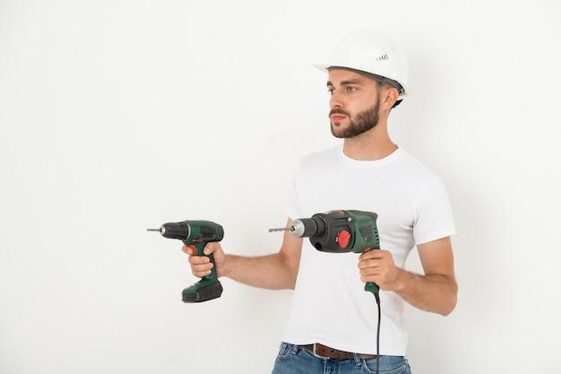 평면에서 리모델링을 준비하는 동안 전원 손 도구를 들고 안전모에 심각한 젊은 수염 수리공