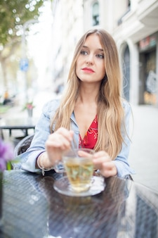 Serious young beautiful woman in summer cafe