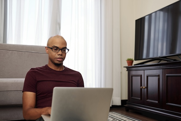 Serious young black bald man sitting on the floor in living room and working on laptop