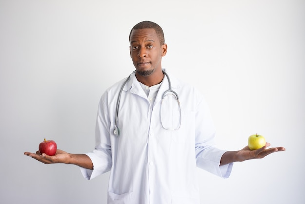 Serious young black male doctor holding green and red apples.