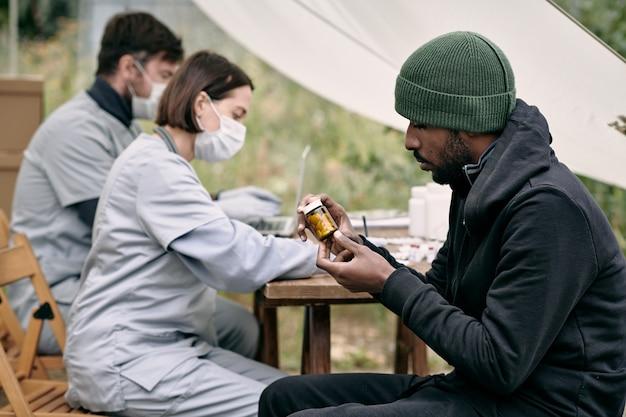 医療従事者のテーブルに座って、ピルのタグを読んで帽子をかぶった深刻な若い黒人難民の男...