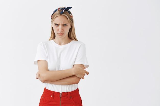 Серьезная молодая блондинка позирует у белой стены