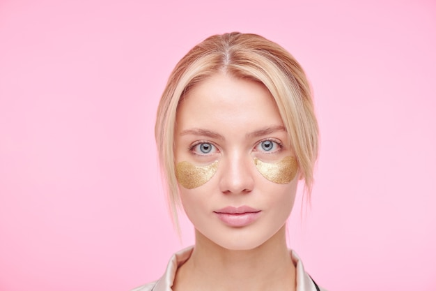 Serious young blond woman with golden revitalising under-eye patches standing against pink wall