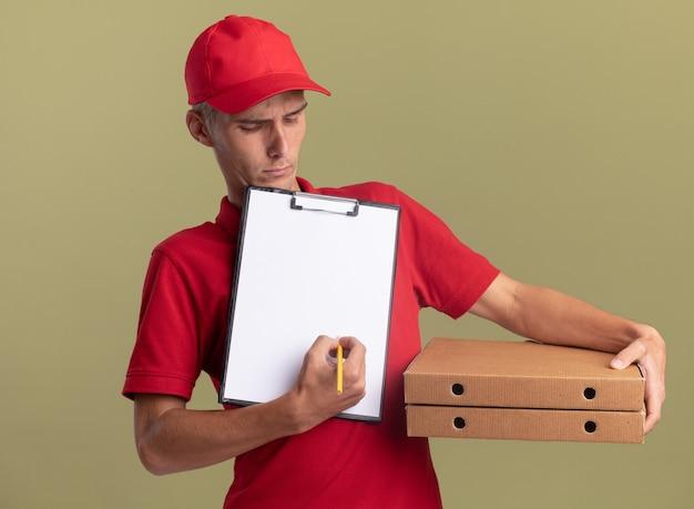 진지한 금발 배달 소년은 피자 상자를 들고 올리브 녹색 벽에 복사 공간이 있는 연필로 클립보드에 씁니다.