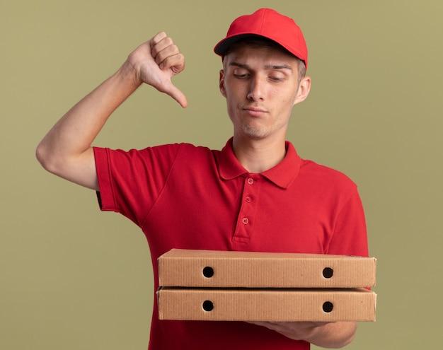 Grave giovane ragazzo delle consegne biondo pollice verso tenendo e guardando scatole per pizza