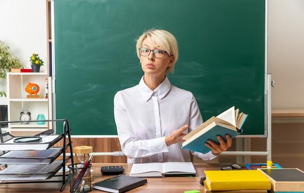真面目な若いブロンドの女性教師は、教室で学用品を持って机に座って眼鏡をかけ、正面を見て開いた本を指しています
