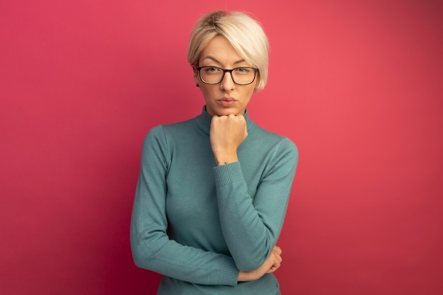 Серьезная молодая блондинка в очках смотрит, положив руку под подбородок, изолированную на розовой стене с копией пространства