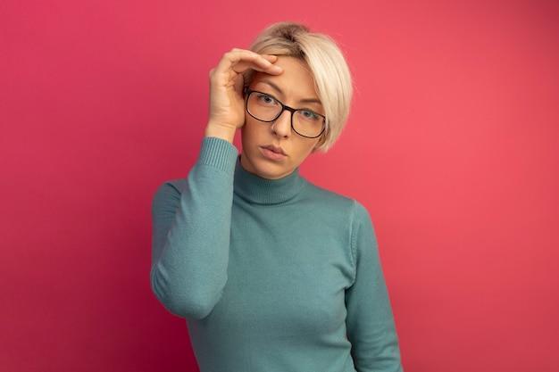 Grave giovane ragazza bionda con gli occhiali toccando la testa