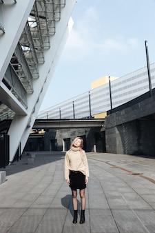屋外で目を閉じて立っている深刻な若いブロンドの女性。