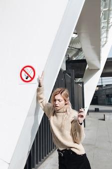 屋外のタバコを持つ深刻な若いブロンドの女性