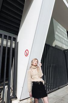 タバコを持つ深刻な若いブロンドの女性