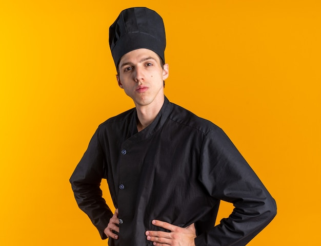 Serious young blonde male cook in chef uniform and cap standing in profile view keeping hands on waist