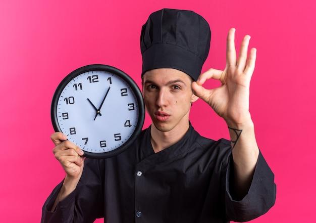 요리사 유니폼을 입은 진지한 금발 남성 요리사와 분홍색 벽에 격리된 확인 표시를 하는 카메라를 보고 있는 모자를 든 모자