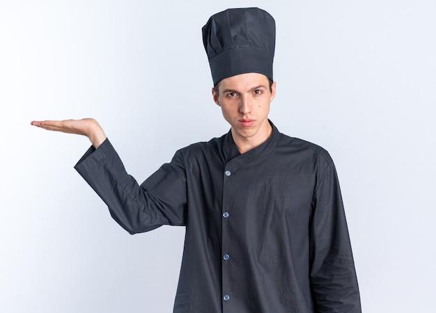 シェフの制服と空の手を示すキャップで深刻な若いブロンドの男性料理人